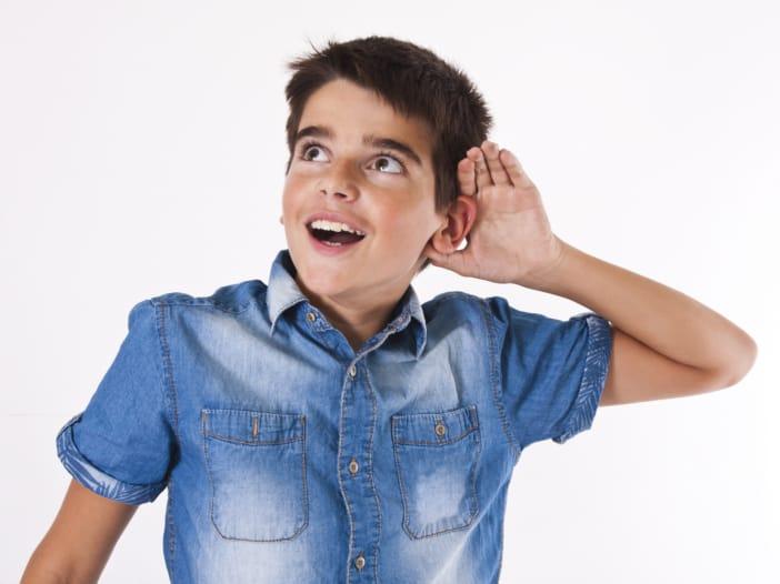 Junge, der die Hand hinter das Ohr hält, um besser hören zu können