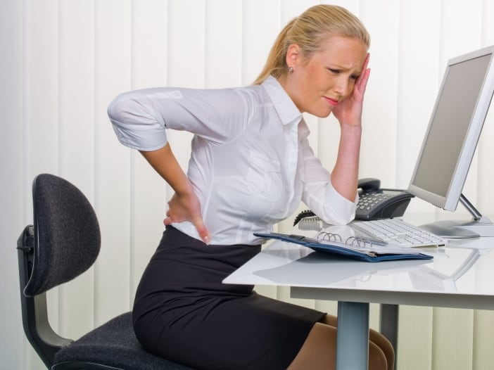 Frau im Büro mit Rückenschmerzen